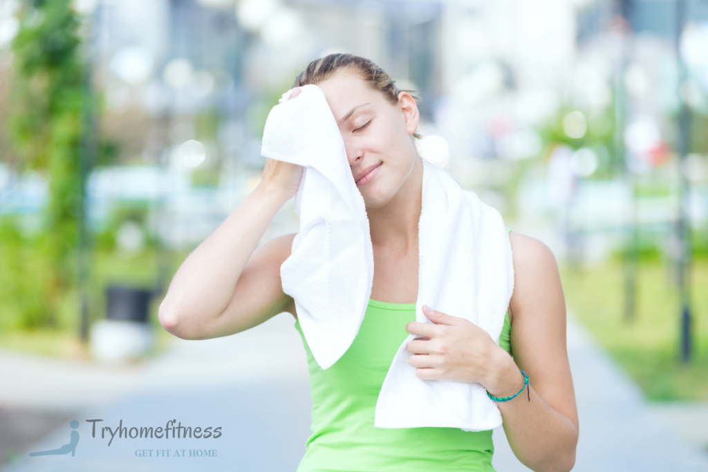 Girl using her best gym towel to swipe the sweat