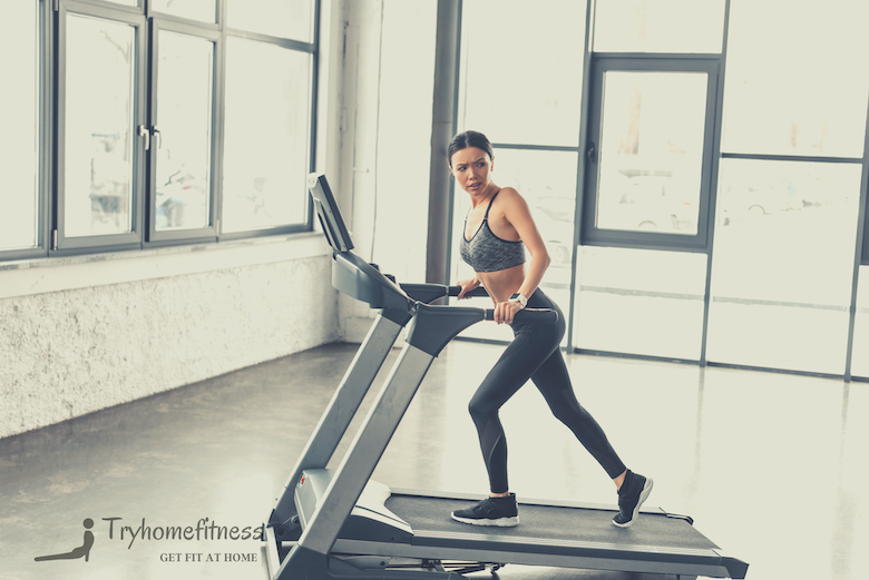 Girl on incline on a treadmill with tv