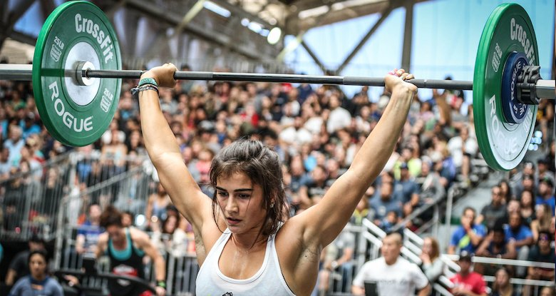 Woman using a Rogue barbell & weights for crosssfit
