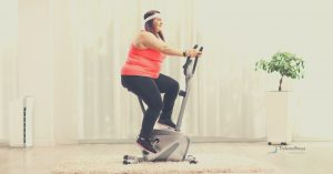 Overweight woman on an exercise bike in her front room