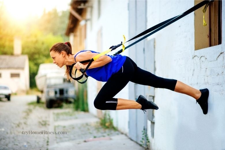 Best suspension trainers can be fixed and used anywhere like this woman on the outside of a external wall