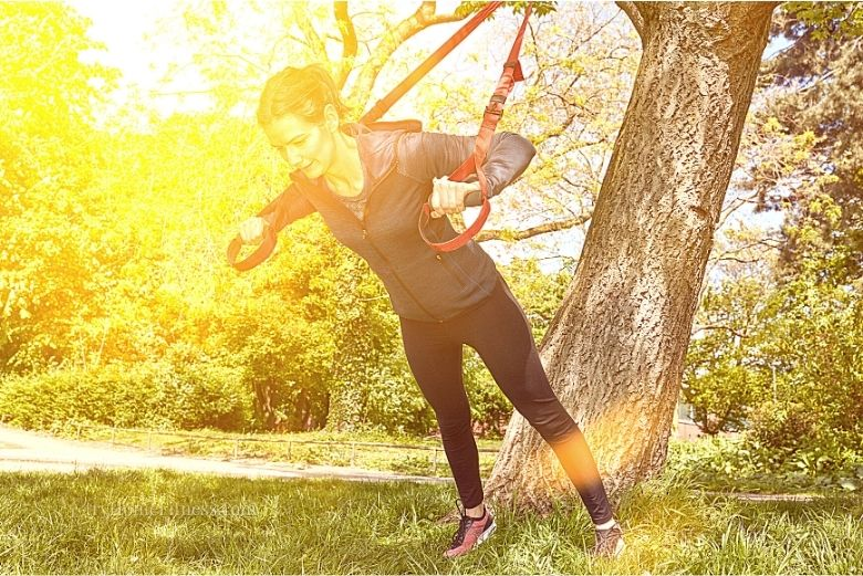 Suspension training benefits one of which shown here where a woman is training outside using a tree